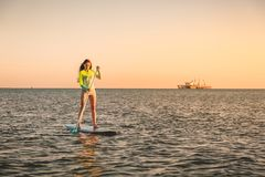 Sporty young girl stand up paddle surfing with beautiful sunset colors. Sporty young girl stand up paddle surfing with beautiful sunset Royalty Free Stock Photos