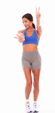 Sporty young lady gesturing winning sign Stock Photo