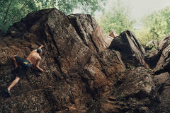 Sporty young man climbing on stone rock Stock Images