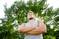 Sporty young man with crossed arms at summer park Royalty Free Stock Photo