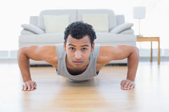 Sporty young man doing push ups in the living room. Portrait of a sporty young man doing push ups in the living room at house royalty free stock images