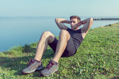 Sporty young man doing sit-ups abs crunches in nature. Royalty Free Stock Photos