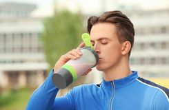 Sporty young man drinking protein shake,. Outdoors stock images