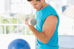 Sporty young man with dumbbell in gym Stock Image