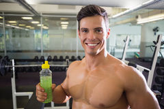Sporty young man with energy drink in gym Stock Photos