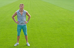 Sporty young man on green training field. Sporty young man standing on green training field, smiling royalty free stock photography