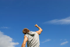 Sporty young man with his arm raised in joy. On blue sky background Stock Photography