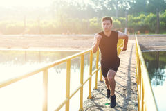 Sporty young man jogger exercising working out at morning outdoors. Royalty Free Stock Images
