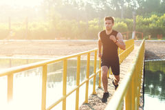 Sporty young man jogger exercising working out at morning outdoors. Stock Photo