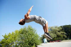 Sporty young man jumping in summer park Royalty Free Stock Photo