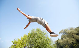 Sporty young man jumping in summer park Stock Image