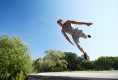 Sporty young man jumping in summer park Stock Photos