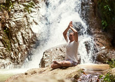Sporty young man practicing yoga near a waterfall in the mountai stock images