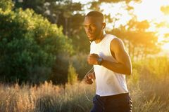 Sporty young man running outdoors in nature Royalty Free Stock Images