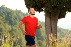 Sporty young man running outdoors Stock Photos