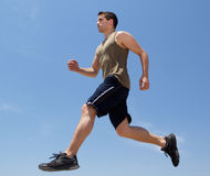 Sporty young man running outside Royalty Free Stock Image