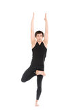 Sporty young man standing in Tree Pose stock photo