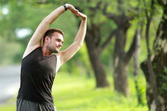 Sporty young man stretching his body before jogging Royalty Free Stock Photo