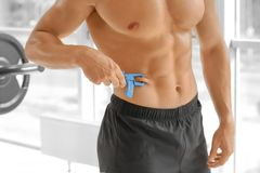 Sporty young man using body fat caliper. In gym stock image