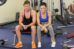 Sporty young man and woman sitting in the gym Stock Image