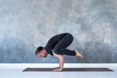 Sporty young man working out, doing handstand yoga asana, Crow Pose or Bakasana royalty free stock image