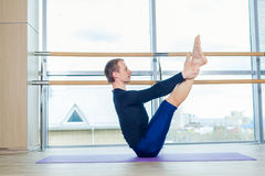 Sporty young man working out, yoga, pilates, fitness training, standing in asana eka pada adho mukha svanasana, one Stock Image
