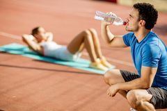 Sporty man drinking water while young woman doing exercise in th royalty free stock photo