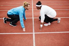 Opposites. Sporty young men and plump women standing on low start in front of one another ready to run Royalty Free Stock Photography