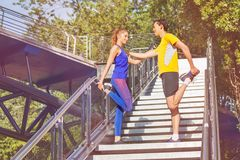 Sporty man and woman stretching legs before jog. Sporty young men and women stretching legs standing at the city stairs opposite to each other in the park Royalty Free Stock Image
