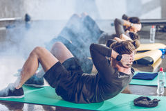 Sporty young people doing abs on yoga mats while exercising stock image