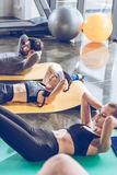 Sporty young people doing abs on yoga mats while exercising. At the gym Stock Images