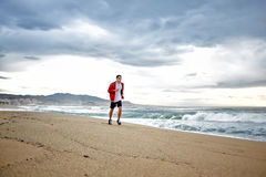 Sporty young runner in sports red windbreaker runs along the beach on beautiful sea background. Morning jogging, fitnes and healthily lifestyle, sport and stock image