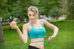 Sporty young woman with apple and measuring tape. Stock Image