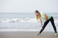 Sporty young woman bend down stretching at the beach Stock Images