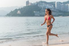 Sporty young woman in bikini running along the beach with bright sunlight and mountainous resort city in background.  Royalty Free Stock Images