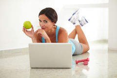 Sporty young woman browsing web and laying Royalty Free Stock Photos