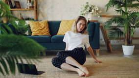 Sporty young woman is doing exercises at home bending forward in seated position then moving legs. Healthy lifestyle. Sporty young woman is doing stretching stock footage