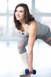Sporty young woman doing lunges with dumbbells Stock Photos