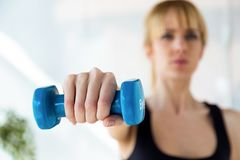 Sporty Young Woman Doing Muscular Exercise With Blue Dumbbells In Physio Room. Stock Photo