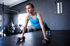Sporty young woman doing push-ups with dumbbells Royalty Free Stock Photo