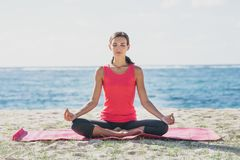 Sporty young woman doing yoga meditation at the beach. Full body portrait of sporty young woman doing yoga meditation at the beach Royalty Free Stock Image