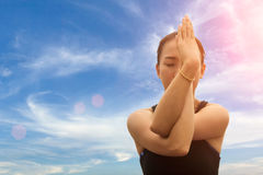 Sporty young woman doing yoga practice isolated on sky background. Sporty young woman doing yoga practice isolated on sky background - concept of healthy life Stock Photography