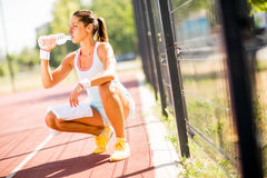 Sporty young woman drinking water Stock Photos