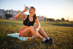 Sporty young woman drinking water. girl sits on a mat and listening music Royalty Free Stock Photo