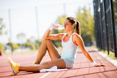Sporty young woman drinking water Stock Images