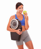 Sporty young woman eating apple for weight loss Stock Images