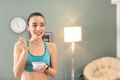 Sporty young woman eating yogurt with berries. After fitness training at home Stock Image