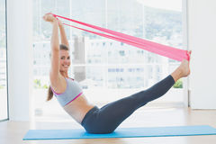 Sporty young woman with exercise band in fitness studio Royalty Free Stock Images