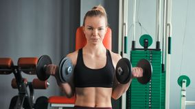 Sporty young woman exercising with dumbbells in the gym.  stock video footage