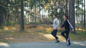 Sporty young woman is exercising outdoors with her male friend running and jumping in park among green trees. Active stock video footage